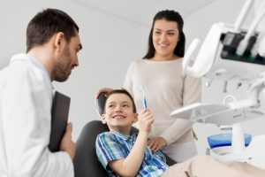 little boy holding toothbrush in dental chair