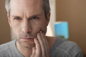 older man with toothache who needs emergency dentist