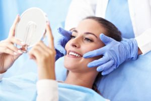 woman admiring her smile in hand mirror after professional teeth whitening