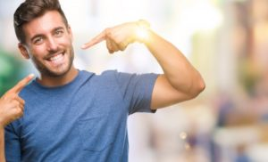 young man pointing to his smile after seeing his cosmetic dentist