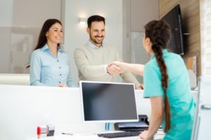 dental team member shaking hands with patient at front desk
