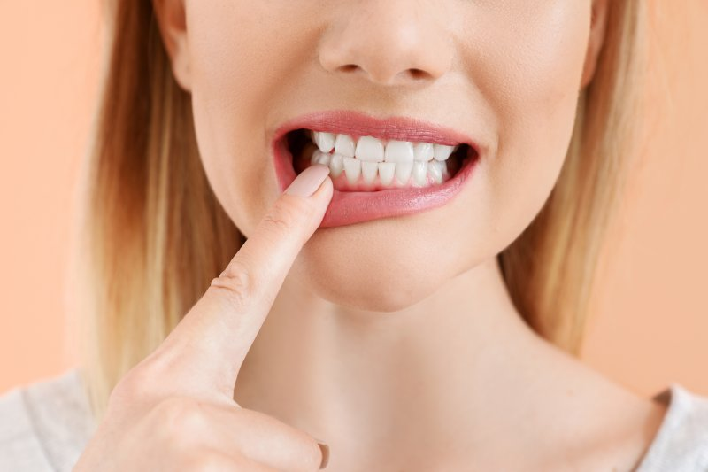 an up-close view of a person pointing to a tooth in the lower arch of their mouth