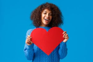 woman smiling and holding a heart