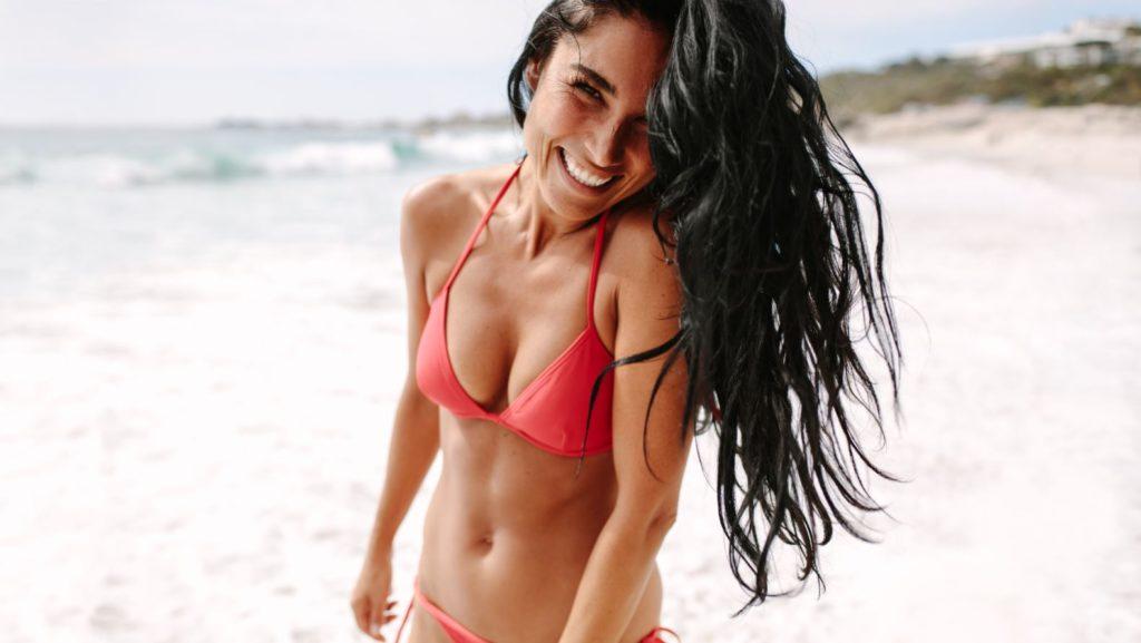 Woman smiling on beach with dental veneers